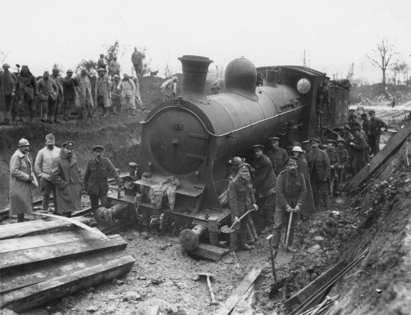 A railway engine which has run off the lines at Maricourt, northern France, during the First World War. With British and (probably) French soldiers. Date: September 1916
