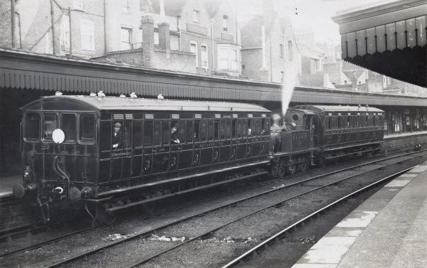 Railway station scene, steam locomotive shunting carriages to platform Date