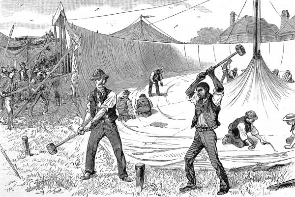 Engraving showing the raising of the 'big top' as a circus arrives in an English country town, c.1886. The two men in the foreground are shown driving a stake into the ground, whilst in the background a number of men work on the canvas