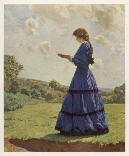 A girl stands in a field reading her book