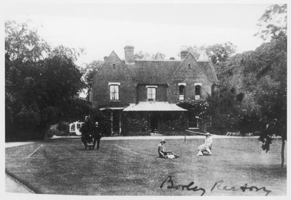 Borley Rectory seen from 'the Nun's Walk' towards the end of the Bull incumbency : members of his family on the tennis court