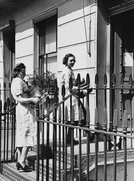 Miss Moorhouse and a friend, both voluntary workers, carry pots and pans into a vacant house which has been requisitioned for the use of refugees
