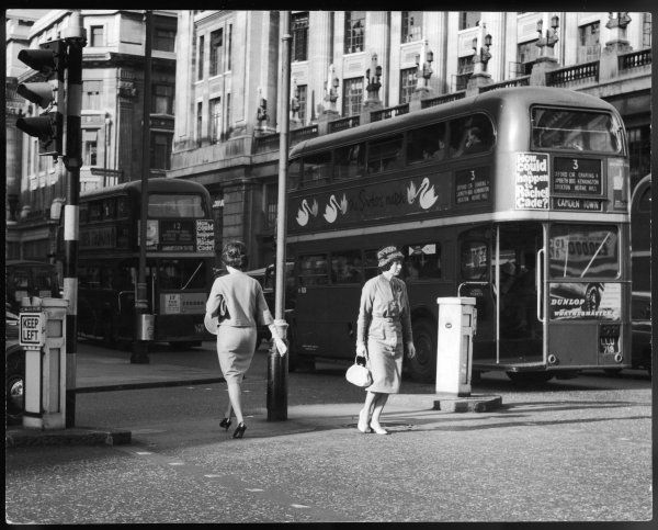 Two women crossing the street in opposite directions, next to two routemaster buses