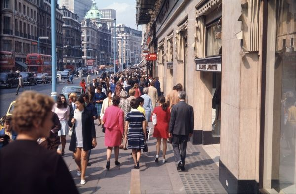 Shoppers in Regent Street, many of the women in colourful outfits, on a hot summer's day
