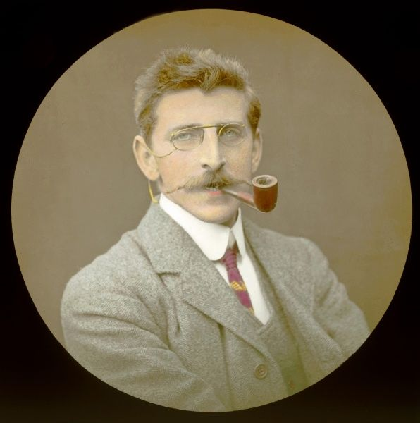 Reginald Malby (1882-1924), official photographer to the Royal Horticultural Society. Seen here in a head and shoulders portrait with a pipe in his mouth
