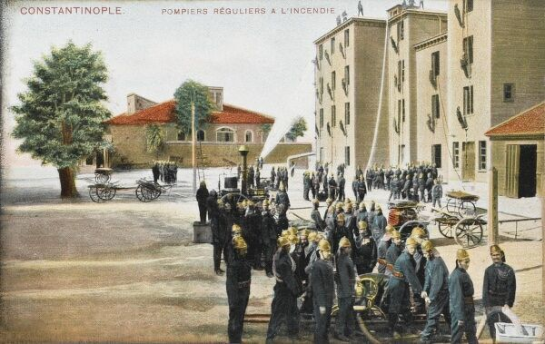 Regular fireman in constantinople drill at their compound, practising scaling the side of a dummy building with long ladders and hosing down a fire. The shining helmets and uniforms are very much at odds with the irregular firmen of the city