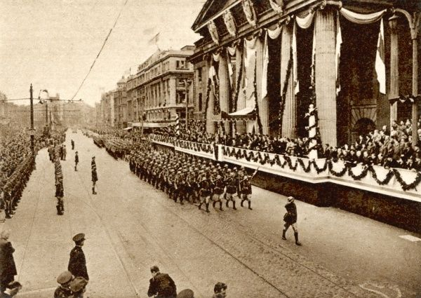 The troops of the new Eire salute as they pass the General Post Office, where the Easter rebels of 1916 proclaimed the Republic, 33 years earlier