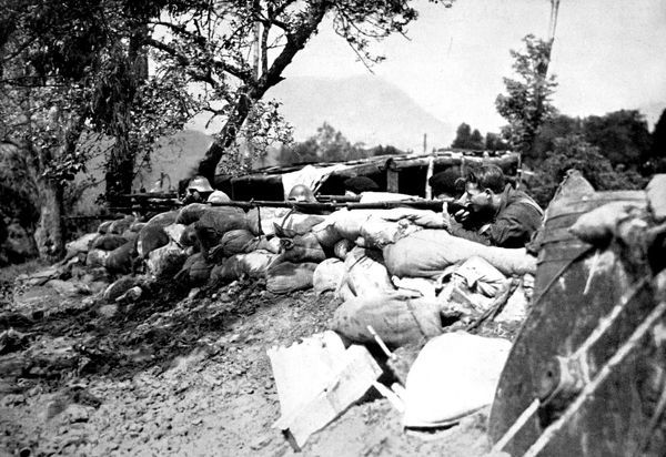 Photograph showing a unit of Republican troops firing from behind a parapet of sandbags, near San Sebastian in the province of Guipuzcoa, 1936