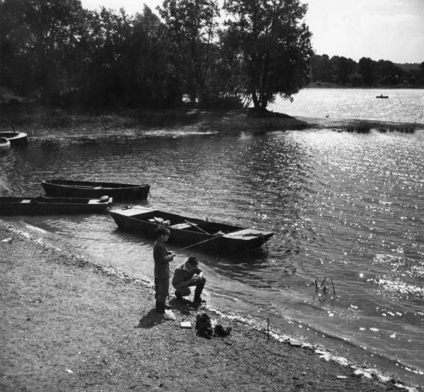 Lads angling on the banks of the glistening waters of Aldenham Reservoir, Hertfordshire, England. Date: 1950s
