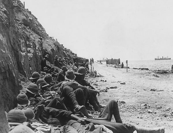 A shell from an Asiatic Annie bursting in the sea. Men resting on the beach road from Cape Helles to Gully Ravine, under shelter of the cliffs at Gallipoli during World War I