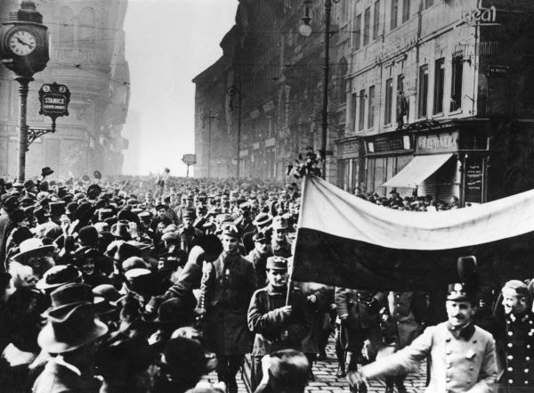 Troops from the Prague garrison, wearing the national cockade in their caps, parade the national colours to the crowds, enthusiasic about Czechoslovakia's independence. Date: 28 October 1918