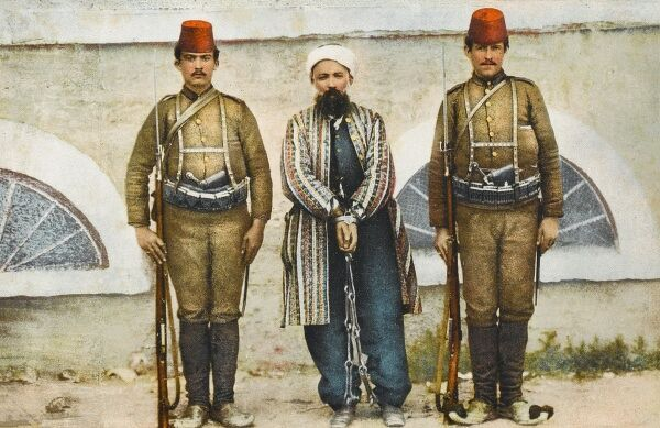 A revolutionary/rebel in Turkey, held in shackles and flanked by two soldiers of the Turkish Army