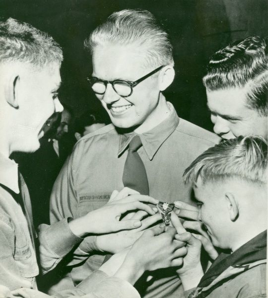 Boys of the 2nd Berkley Boy Scout Troop, California, December 8 cluster round to feel the Eagle Scout badge of Rich Wotherspoon, 20