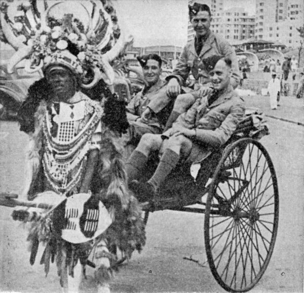Ricksha in Durban, South Africa, during World War Two, with Zulu ricksha 'boy' and passengers of three RAF air cadets