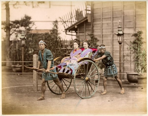 Two well-dressed Japanese ladies take a ride in a rickshaw powered by two rickshaw drivers