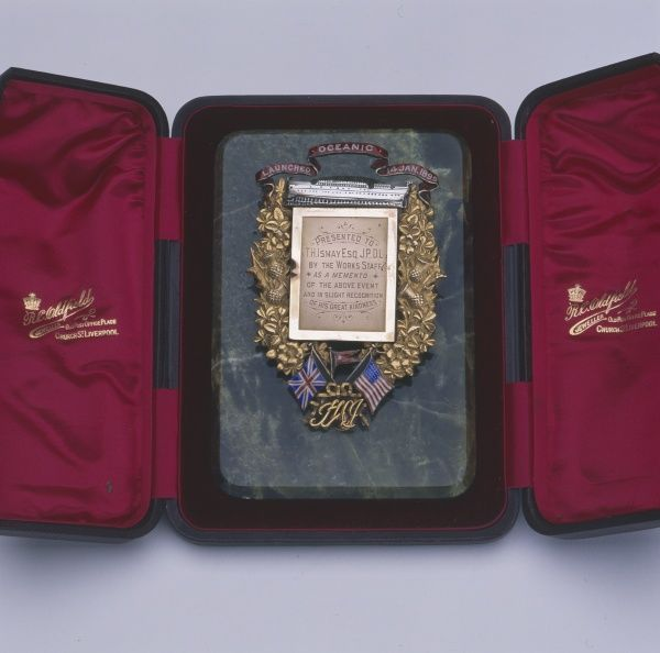 A medal presented to Thomas Henry Ismay to mark the launch of the RMS Oceanic on 14 January 1899. The ornate gilt design includes the British and American flags. The presentation box is from RC Oldfield jewellers of Church Street, Liverpool