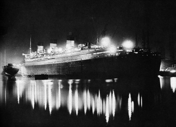 RMS Queen Mary, the new giant Cunard White Star Liner, floodlit at night, before her maiden voyage. Date: early 1936