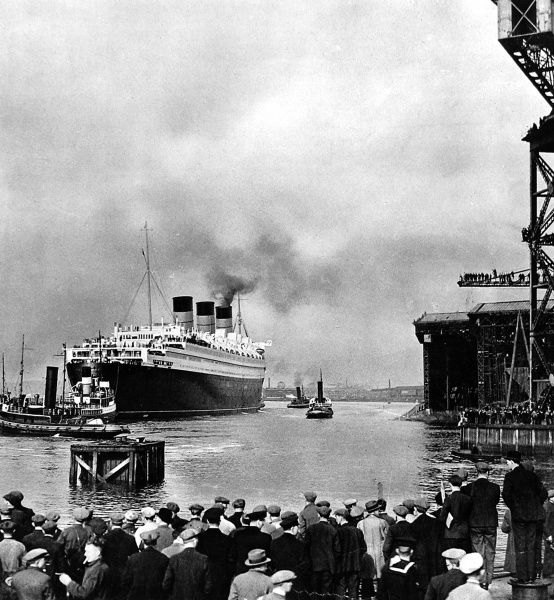 Photograph of the R.M.S. 'Queen Mary' leaving John Brown's shipyard, Clydebank, for Greenock on 24th March 1936. Several of the seven tugs involved in manoevering the 'Queen Mary' down the Clyde are visible in the shot