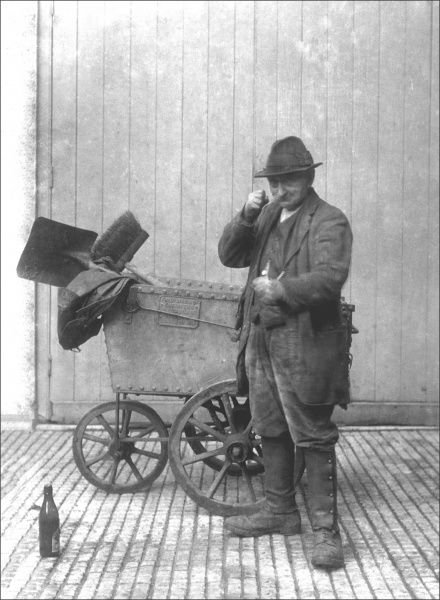 A rather ragged dustman or road sweeper with his sweeping brushes and shovel, cart and empty bottle of ale! Photograph by Ralph Ponsonby Watts