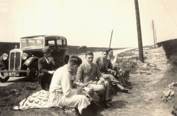 Five chaps have a roadside picnic alongside their parked Lanchester (10 HP) car