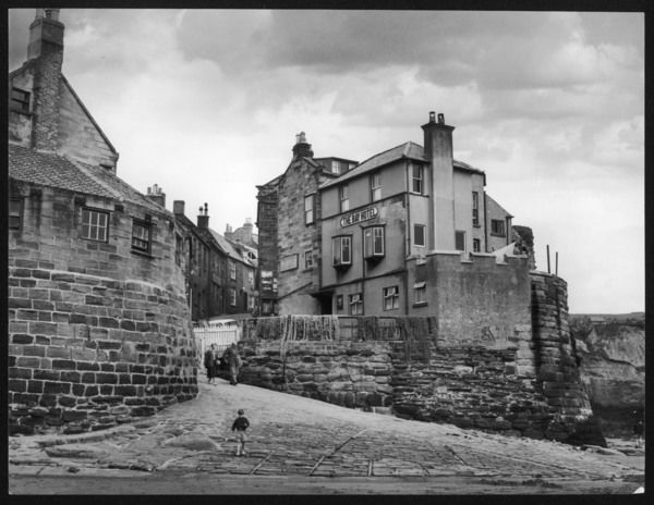 A boy runs ahead of his grandparents to the beach at Robin Hood's Bay, North Yorkshire, a charming old town from whence, legend has it, Robin Hood escaped by sea