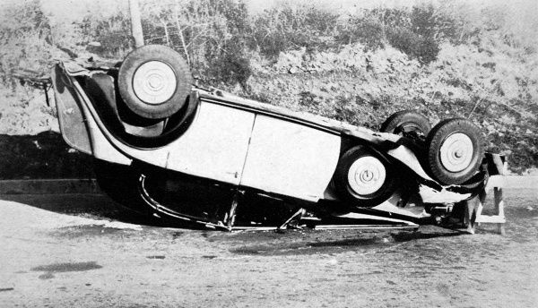 A photograph of an upturned Rolls Royce, belonging to Mr. Benjamin Guinness on the road between Pisa and Rome. All the passengers were saved due to the body pillars in the car which withstood practically the whole weight of the car