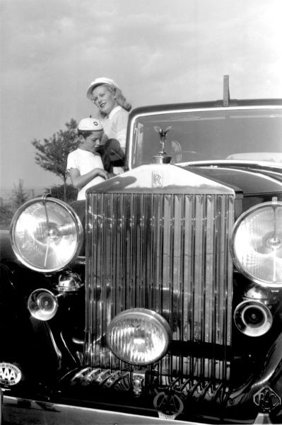 A superb photograph of the front of a Rolls Royce Silver Wraith, with dominant headlamps and horns, the Spirit of Ecstasy mascot. A glamorous woman and her smartly-attired son stand alongside