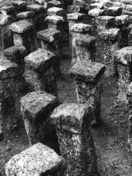 Roman hypocaust pillars, part of an underfloor and walls 'central heating' system, in the remains of a villa at Chedworth, Gloucestershire, England. 3rd - 4th century A.D. C.1950