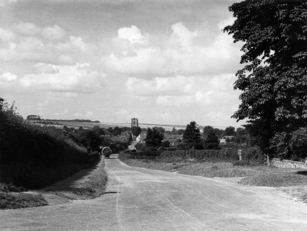 Wold Gate or Wod Yat, an ancient Roman trackway following the line of the Roman road over the Yorkshire Wolds, England. Here dipping into Kilham Village. Date: 1950s