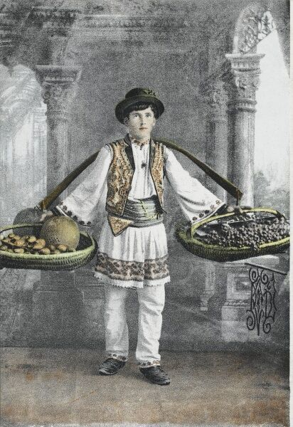 A young Romanian boy in National costume carrying two large baskets filled with fruit (including melons, figs and grapes). He is posing in a studio with a classical backdrop, possibly rather out of keeping with his normal working environment