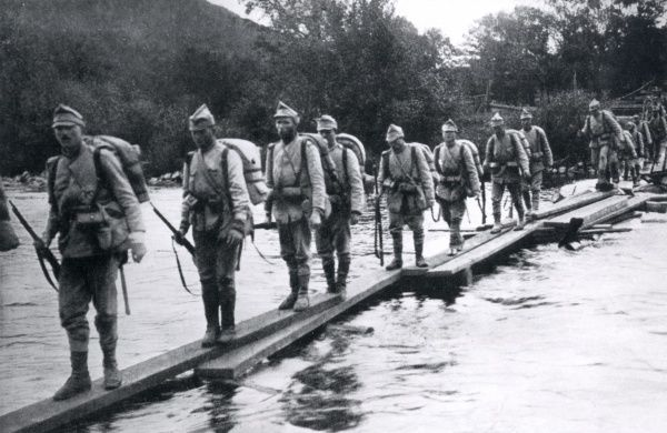 Romanian soldiers retreating during the First World War. They are crossing a river by means of a makeshift wooden bridge. Date: 1916