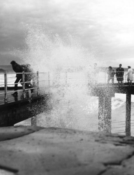 Holidaymakers getting soaked by waves crashing against a pier at a British seaside resort! Date: 1960s