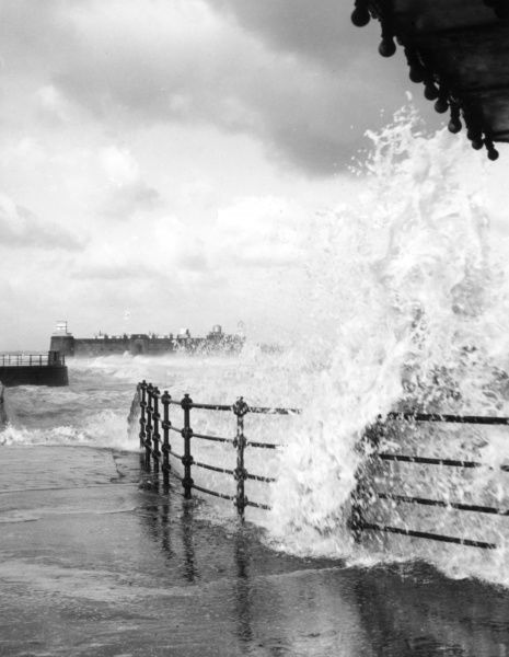 A rough sea study at New Brighton, Cheshire, England, showing waves crashing against the promenade railings. Date: 1960s
