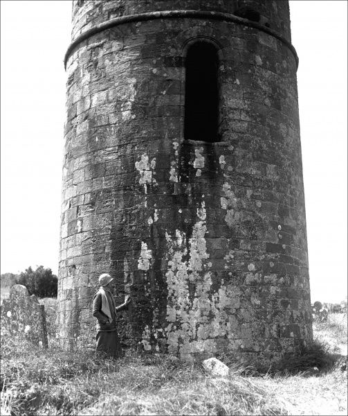 A woman wearing a cloche hat stands in front of an old round tower somewhere in the Devon countryside. Photograph by Ralph Ponsonby Watts