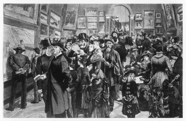 A crowded scene of smartly- dressed men, women and children visiting the Royal Academy in London to look at and discuss the paintings