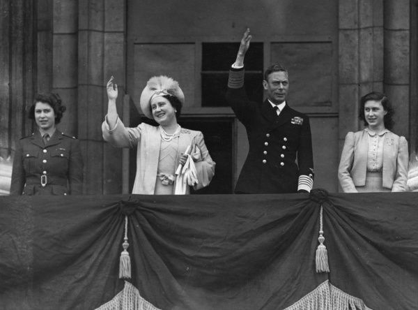 King George VI, Queen Elizabeth (later the Queen Mother) together with their daughters, Princess Elizabeth (later Queen Elizabeth II) in ATS uniform and Princess Margaret Rose on the balcony of Buckingham Palace waving to crowds on VE Day, 8