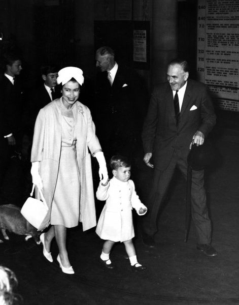 Queen Elizabeth holds two year old Prince Andrew's hand at Euston Station as they leave for Balmoral, escorted by Mr. H.C Johnson, General Manager, London Midland region. In the background are the Duke of Cornwall and Crown Prince Gustav of Sweden