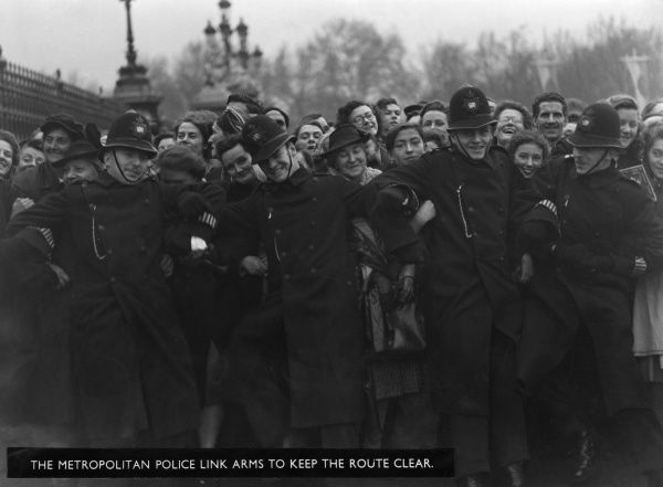 A row of jovial police officers link arms to prevent the crowd surging forward during the royal wedding of 1947
