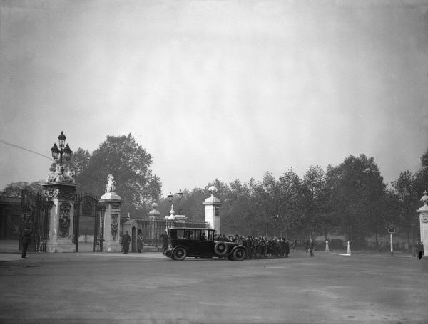 A crowd gathers at the gates of Buckingham Palace to watch King George V and Queen Mary driving past. Date: early 1930s