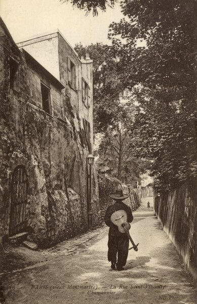 An itinerant singer, his guitar strapped to his back, strolls along Rue Saint Vincent - Montmartre, Paris, France. Date: circa 1910s