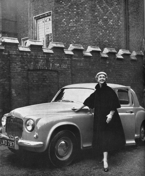 A girl wearing a Rumonte mirror velvet coat with push up sleeves and a pretty Byronic collar, stands next to a Rover 75 saloon. Her lemon yellow melusine hat is by Connor. Date: 1953