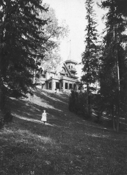 A little girl stands on a grassy slope beneath an aristocratic country house in Russia