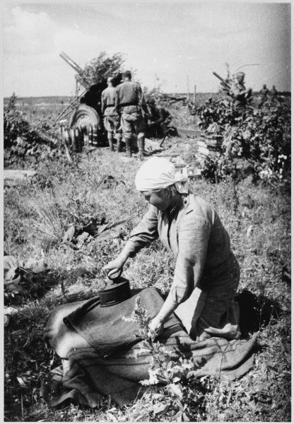 Soviet soldier ironing her uniform at an artillery position