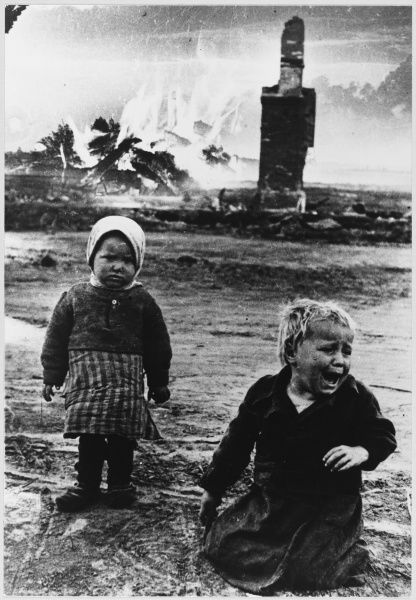 Two Orphaned children wander alone among the smouldering ruins of their town