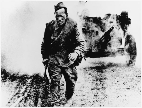 A Soviet soldier moves forward, accompanying a field gun