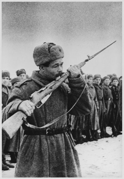 A Soviet soldier makes the 'Soldiers' Oath', kissing his rifle