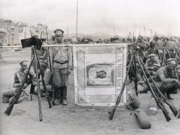 Russian soldiers with the regimental colour at Salonika (Salonica, Thessaloniki, Greece) during the First World War. The banner is made of white silk, with an embroidered motto saying 'God is with us', and an image of Christ at the centre