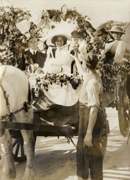 A rustic wedding in Kent -- the bride sits on a horse-drawn cart which has been decorated with garlands, and receives a lucky horseshoe from the village blacksmith
