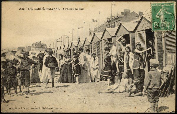 Bathers, friends and families beside a row of bathing huts on the sands of Les Sables d'Olonne, France
