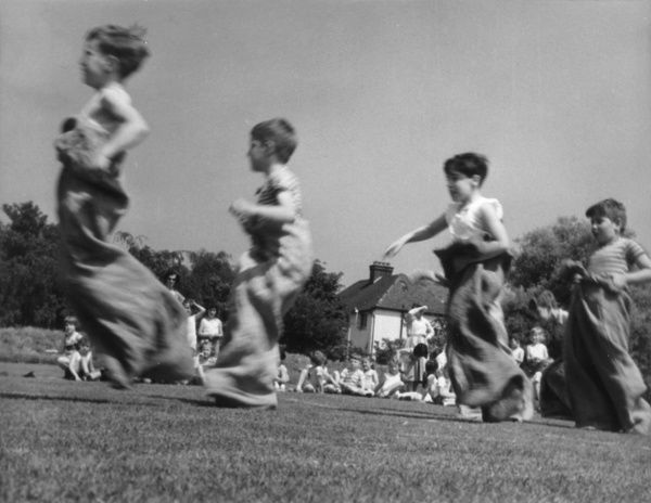 Children compete in a sack race, during a school sports day